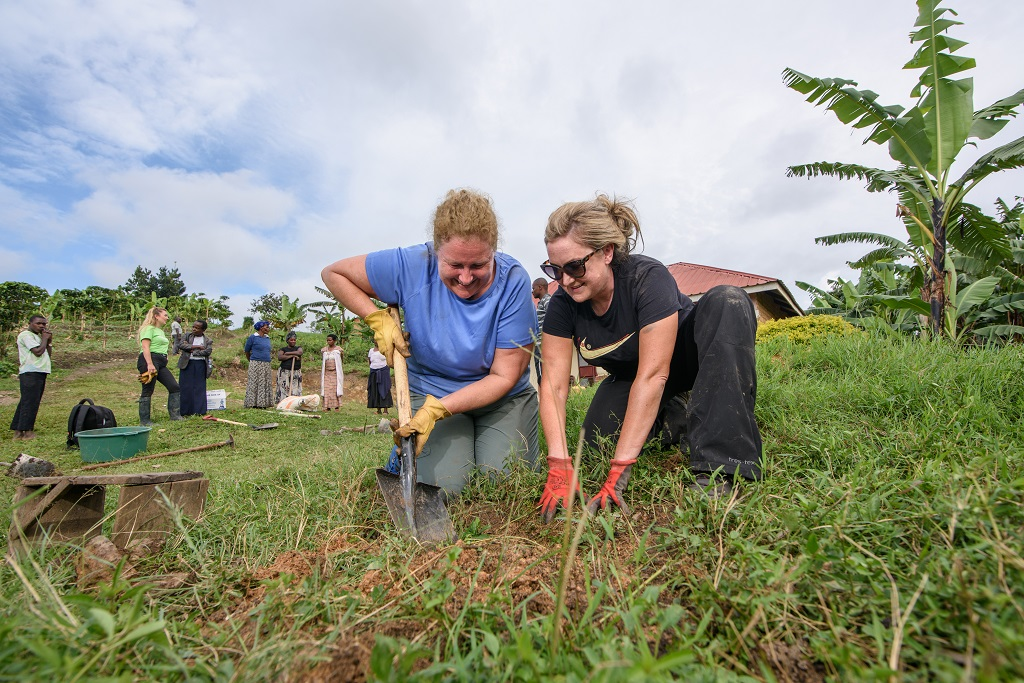 Helen Brierley and Jenni Gowdy work together to plant a fruit tree.