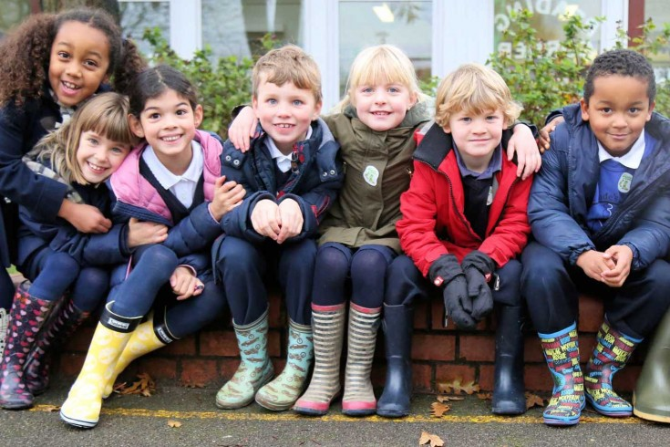 Children in wellies sitting on a low wall